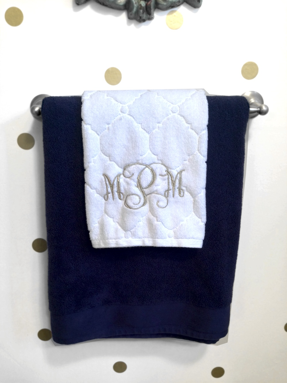 Embroidered white and navy towels with gold metallic thread.