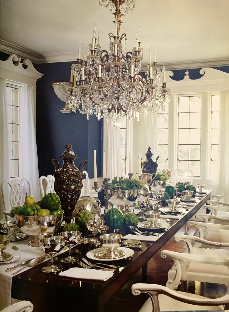 Mary McDonald's own dining room. She uses a dark gray on the walls with white trim. Glossy Chippendale chairs serve as a great juxtaposition to the matte walls. A fantastic French chandelier is the glamorous focal point, and she has set her table with her personal silver collection which is simple and chic. I'd love to sit at that table.
